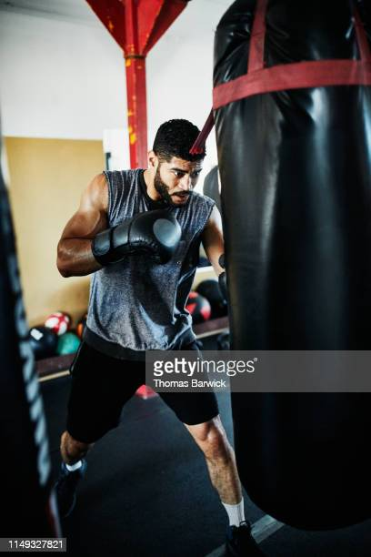 male boxer working out on heavy bag in boxing gym - boxing shorts stock pictures, royalty-free photos & images