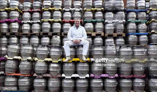 Male Brewer Sitting On Kegs