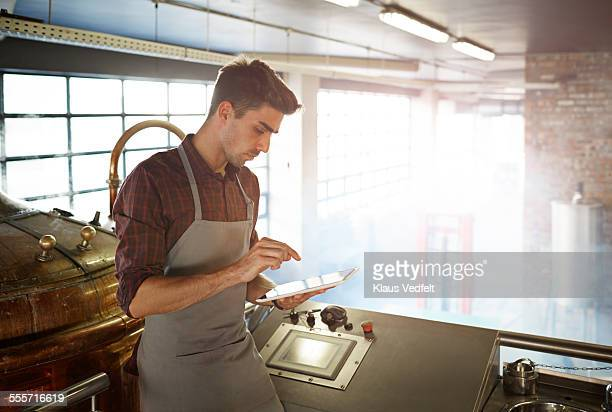 Male brewmaster operating using tablet at brewery