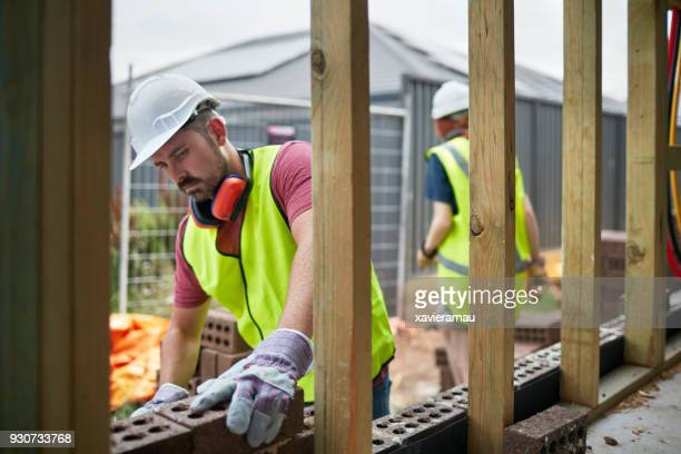 Male bricklayer cementing bricks at site