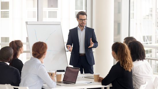 Male business coach speaker in suit give flipchart presentation 1151593834