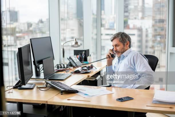固定電話事務所を利用した電話で男性経営者 - 加入電話 ストックフォトと画像