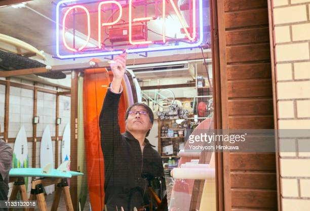 male business owner turning on neon open sign in shop window - opening event stock pictures, royalty-free photos & images