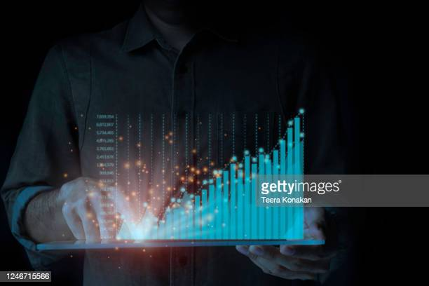 a male businessman is standing by a tablet analyzing the ongoing upwards of the graph. a rapidly changing business concept on a black background. - data stock pictures, royalty-free photos & images