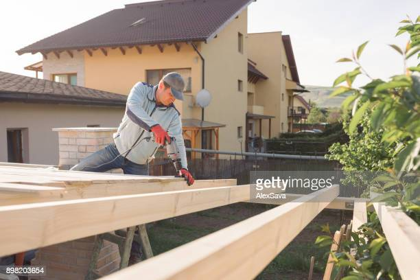 Male cadult working on house construction