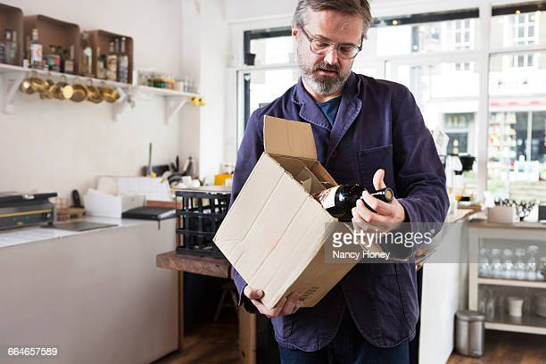 Male cafe owner selecting bottle of red wine