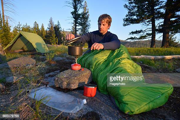 Male camper in sleeping bag prepares a meal on camping stove at Midnight Ridge, Colville National Forest, Washington State, USA