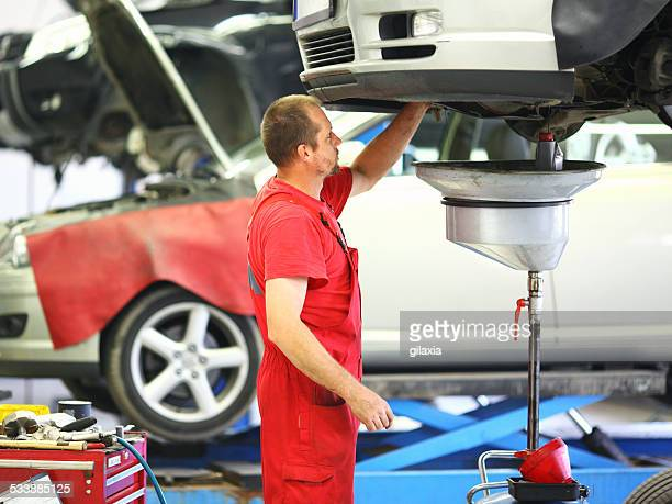 Male car mechanic changing engine oil.