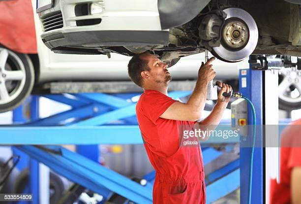 Male car mechanic repairing break system on vehicle.