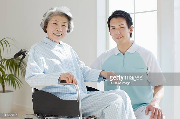 Male care worker and senior woman in wheelchair