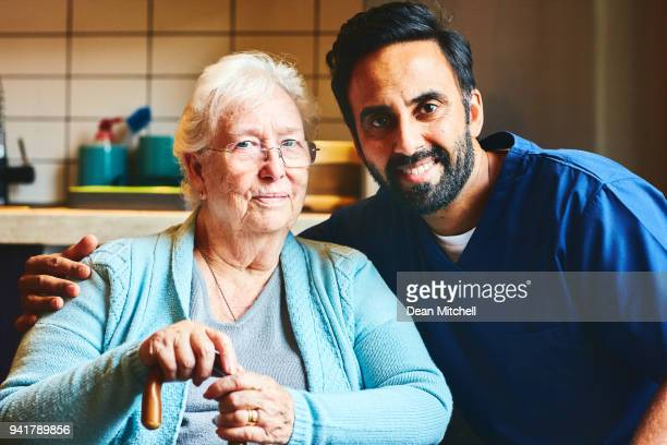 Male carer with elder woman at care home