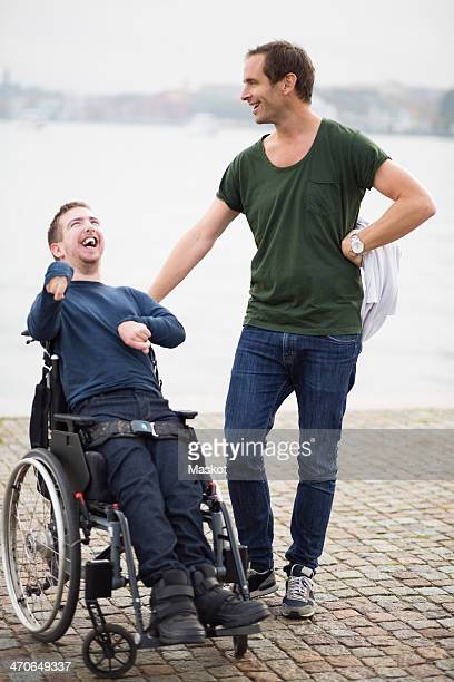 Male caretaker standing with happy disabled man on wheelchair by lake
