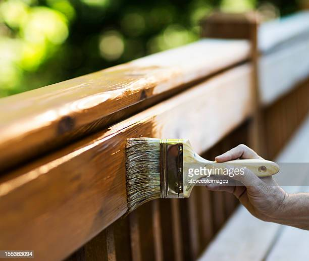 Male Carpenter Applying Varnish To Wooden Furniture.