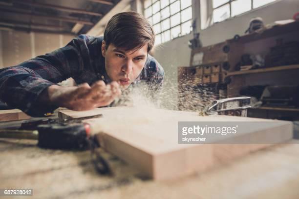 Männliche Zimmermann Abblasen Sägemehl während der Arbeit an einem Stück Holz in einem Workshop.