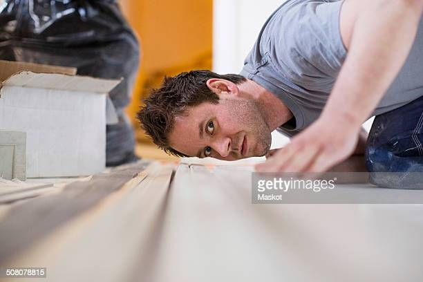 Male carpenter checking wooden plank at site