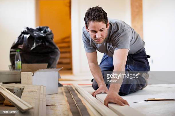 Male carpenter examining wooden plank at site