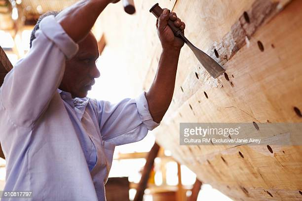 Male carpenter hammering chisel on dhow boat, Sur, Oman, Middle East