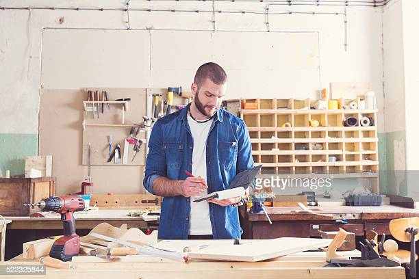Male carpenter in a construction workshop, analyzing draft