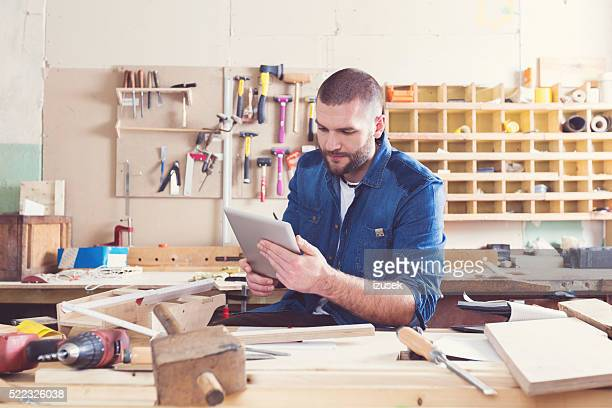 Male carpenter in a construction workshop, using a digital tablet