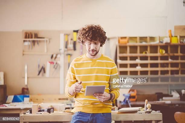 Mâle charpentier dans un atelier de construction, à l'aide d'une tablette numérique