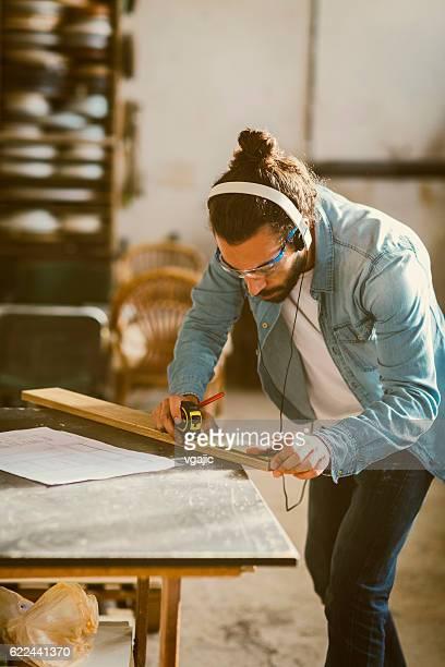 Male Carpenter Measuring Plank In His Workshop