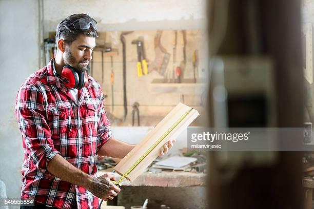 Male carpenter measuring the board