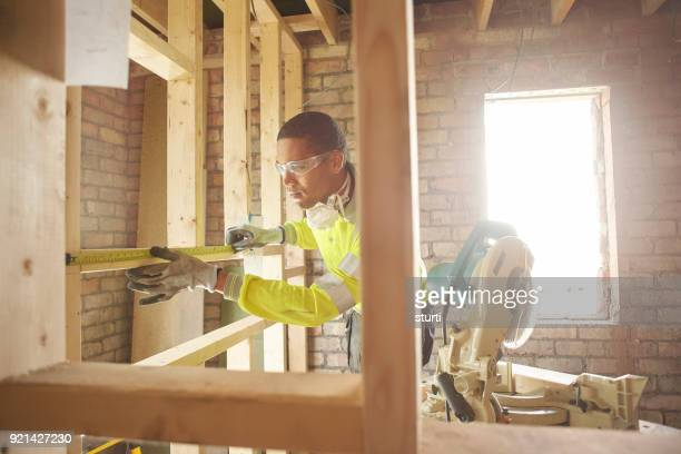 male carpenter measuring the studwork - black glove stock pictures, royalty-free photos & images