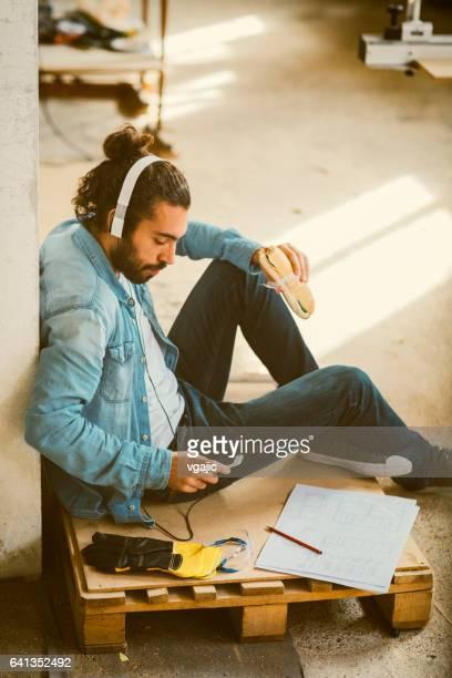 Male Carpenter on lunch break In His Workshop