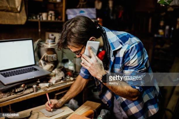Male carpenter on phone and laptop at the workshop