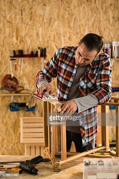 Male carpenter sanding wooden chair