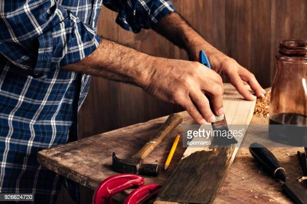 Male carpenter stain dying lumber plank in home workshop