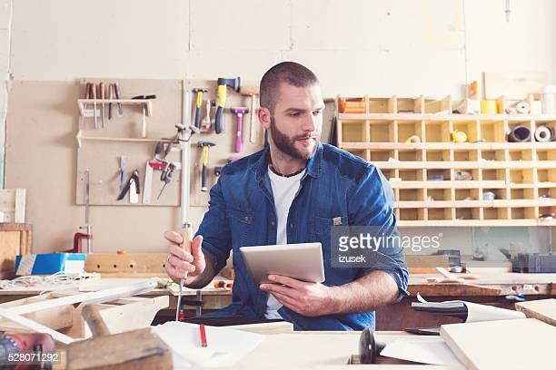 Männlich Zimmermann mit einem Digitaltablett in einer Konstruktion workshop
