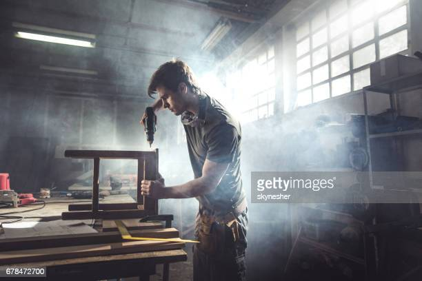 male carpenter using drill to repair a chair in a workshop. - drill stock pictures, royalty-free photos & images