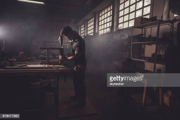 male carpenter using drill to repair a chair in a workshop. - craftsman stock photos and pictures