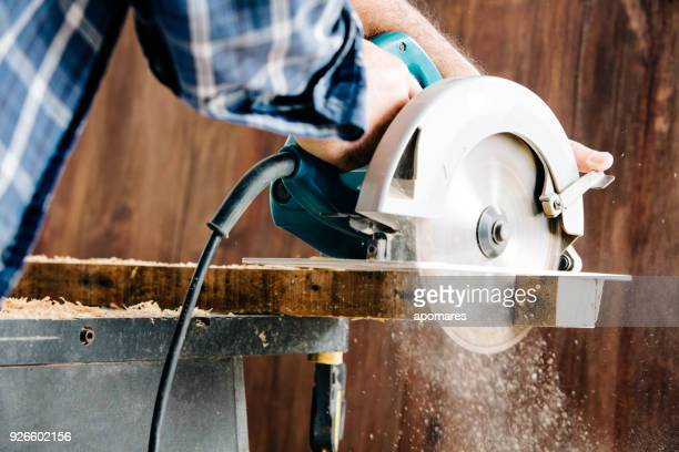 male carpenter using electric circular saw in home workshop with wood chips flying - circular saw stock photos and pictures