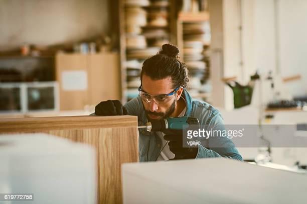 Male Carpenter Using Electric Screwdriver In His Workshop