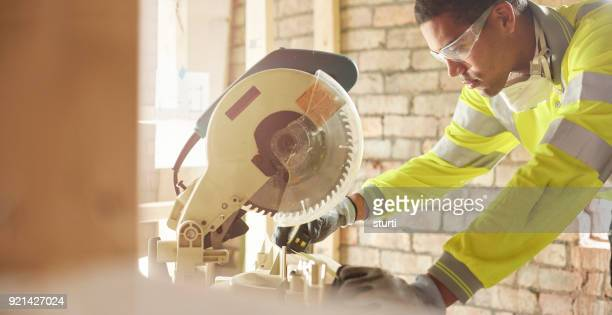 male carpenter with chopsaw - black glove stock pictures, royalty-free photos & images
