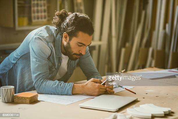 male carpenter working in his workshop - man bun stock pictures, royalty-free photos & images