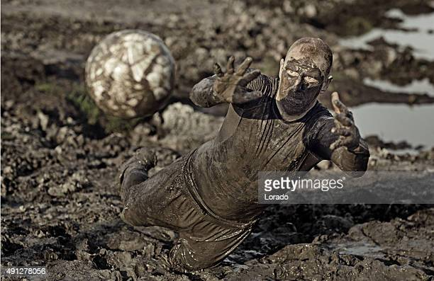 male catching football in mud