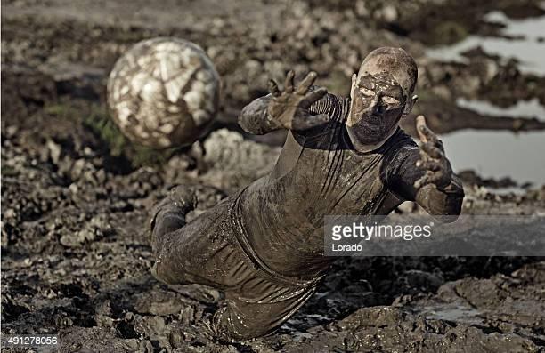 Männliche auffälligen Fußball mit Schlamm