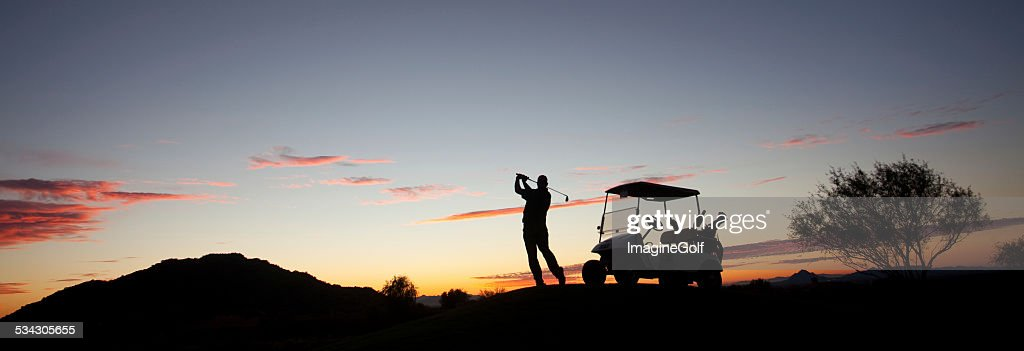 Male Caucasian Golfer Swinging A Golf Club with Cart : Stock Photo
