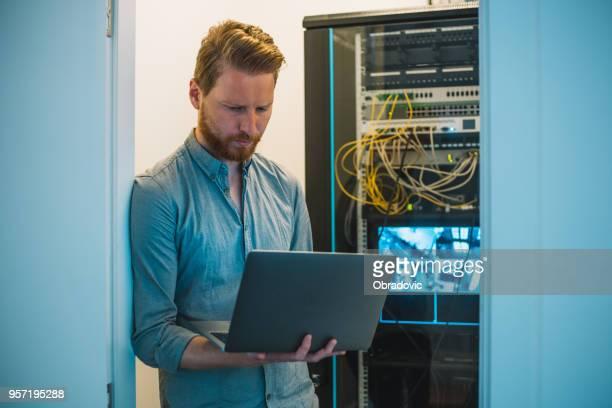 Männlichen kaukasischen IT-Techniker mit Laptop im Serverraum