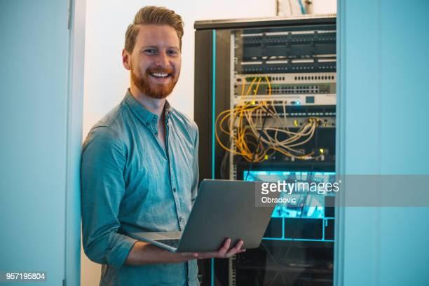 macho caucasiano-técnico usando o laptop na sala do servidor - técnico - fotografias e filmes do acervo