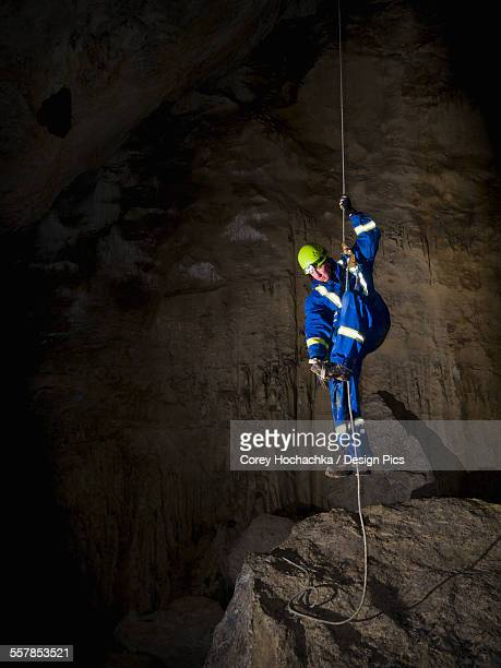 male caver climbing a rope to exit a cave - speleology stock pictures, royalty-free photos & images