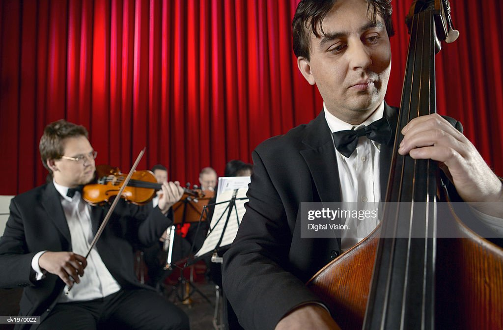 Male Cellist Performing on Stage With an Orchestra : Stock Photo