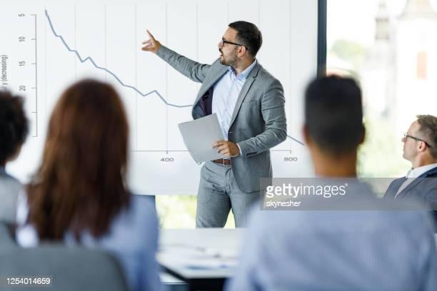 ceo maschile che parla di crisi economica alla presentazione in ufficio. - finanza foto e immagini stock