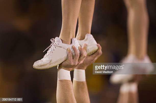 male cheerleader lifting female cheeleader above his head, close-up - vertrauen stock-fotos und bilder