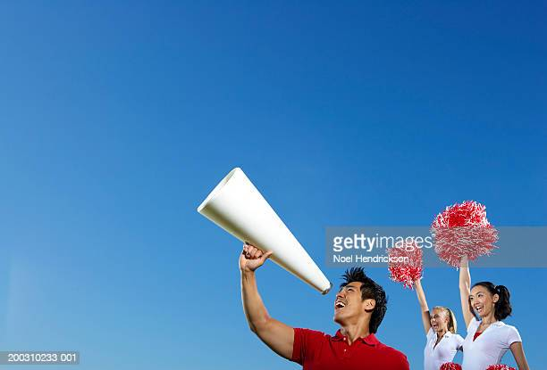 male cheerleader using megaphone, two female cheerleaders behind - pom pom stock pictures, royalty-free photos & images