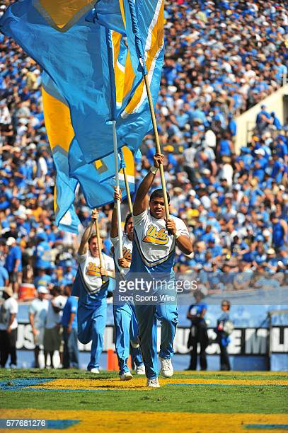 Male cheerleaders run with flags after a score during a college football game between the Oregon Ducks and the UCLA Bruins played at the Rose Bowl in...