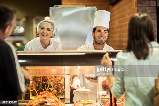 Male chef and assistant helping clients at food display